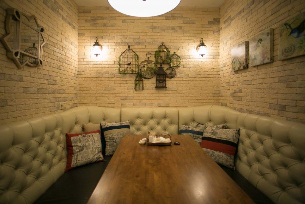 Одна из кабинок кафе декорирована увитыми цветами птичьими клетками