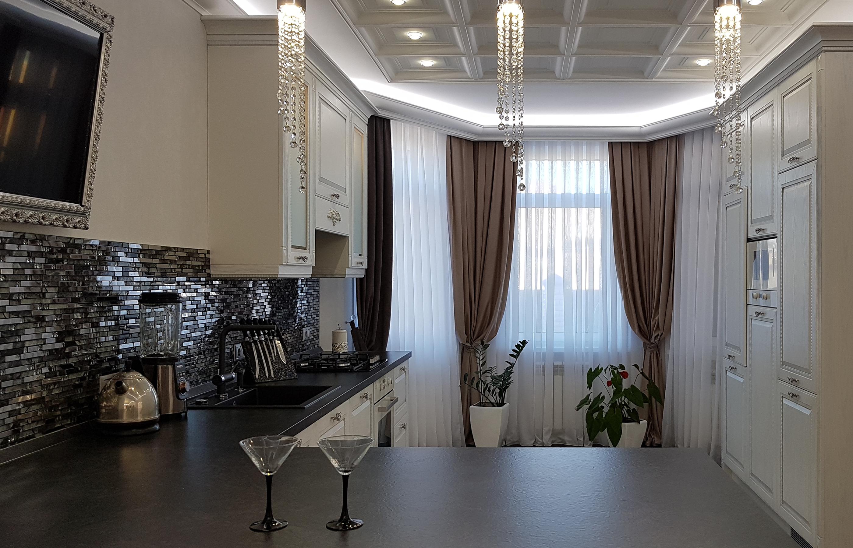 Стеклянная мозаика тонко оттеняет белоснежные, с серебристым патинирование фасады кухонных шкафчиков